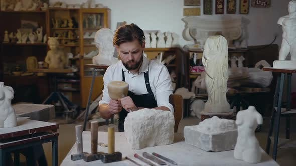 Young Master with Well-Groomed Beard Scraping the Remains of Limestone with the Brush