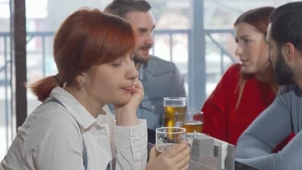 Traurige Frau trinkt Bier im Pub