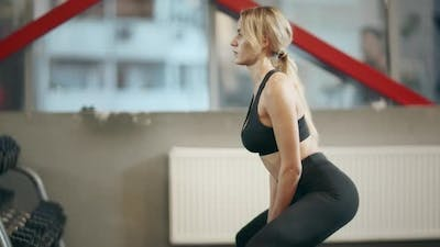 Sportswoman Squatting with Dumbbells in Fitness Center