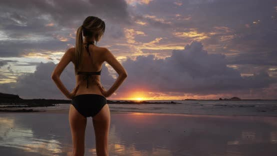 Thumbnail for Young millennial woman in bikini with back to camera standing on beach at sunset