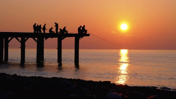 Thumbnail for Silhouettes of Fishermen with Fishing Rods at Sea Sunset Sitting on the Pier, Slow Motion