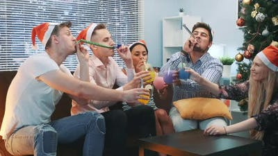 Best Friends Making Cheers and Blowing Party Whistle on Christmas Party