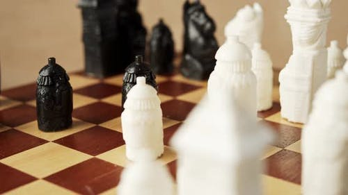 Black and White Chess Pieces on a Wooden Chessboard