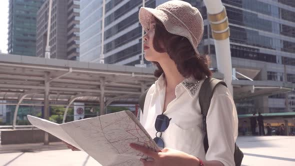young Asian backpacker woman direction and looking on location map while traveling at Bangkok.