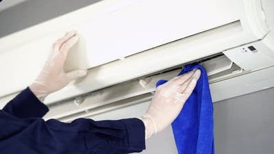 close up technician service cleaning the air conditioner with cloth