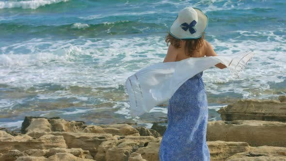 Thumbnail for Young Elegant Woman Holding Scarf in Wind, Ocean Waves Crashing on Rocky Beach