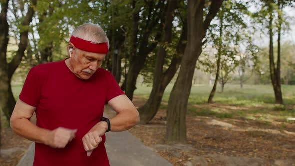 Elderly Sport Man Stops After Running, Using Smart Watch, Checking Heart Rate During Fitness