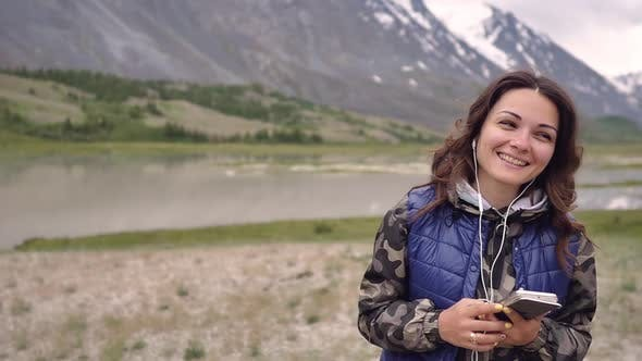 Woman Tourist in Headphones Dancing on a Background of Mountains and Scenery. Tourist Trip