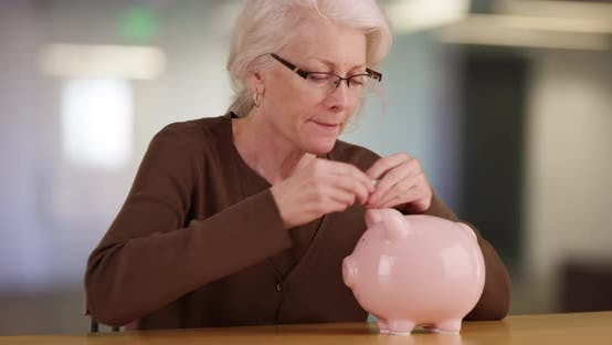 Mature woman putting dollar into piggy bank saving money for retirement