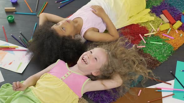 Thumbnail for Best Friends Lying on Colorful Carpet and Laughing, Enjoying Cool Holidays