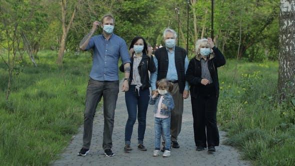 Große Familie im Park nimmt medizinische Masken nach Coronavirus-Quarantäne Ende