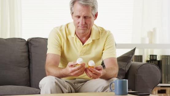 Thumbnail for Senior man holding prescription bottles