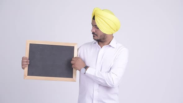 Thumbnail for Stressed Bearded Indian Sikh Businessman Holding Blackboard and Giving Thumbs Down