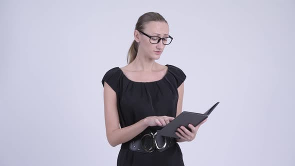 Cover Image for Blonde Businesswoman Talking While Reading Book