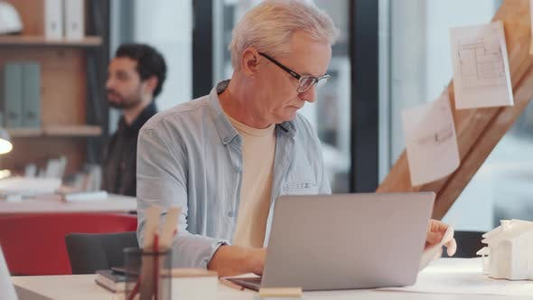 Thumbnail for Senior Male Architect Working on Laptop and Examining Documents