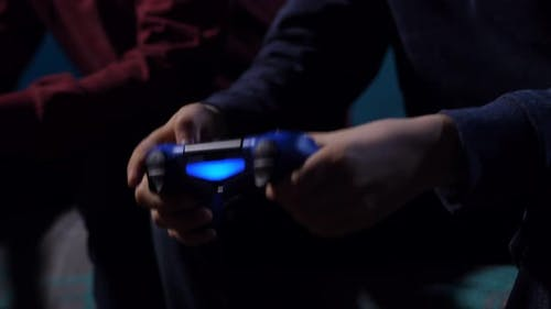 Hands of Boy Holding Game Controller
