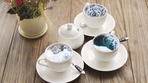Deep Blue Stormy Ocean Locked Into Small White Cups. Thundery Restless Sea Inside Crockery. Waves