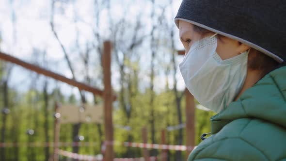 Thumbnail for A Boy in a Medical Mask Standing Near a Closed Playground