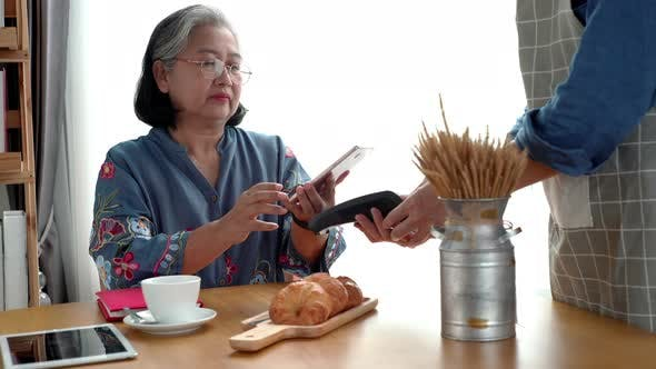Thumbnail for Elderly Asian Woman Using a Mobile Phone Smart Payment 02