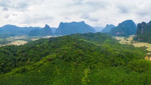 Aerial: panorama of scenic cliffs rock pinnacles tropical jungle rice paddies