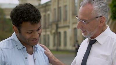 Experienced Mentor Praising His Apprentice for Efforts, Power of Teamwork