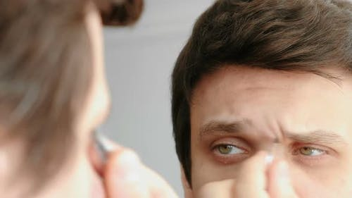 Young Man Plucking His Eyebrows with Tweezers. Styling Eyebrows.