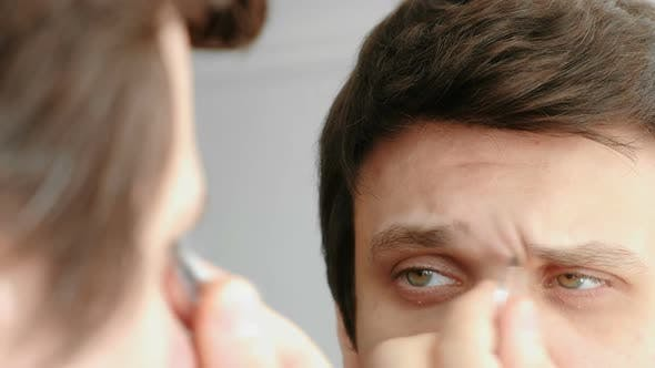 Thumbnail for Young Man Plucking His Eyebrows with Tweezers. Styling Eyebrows.
