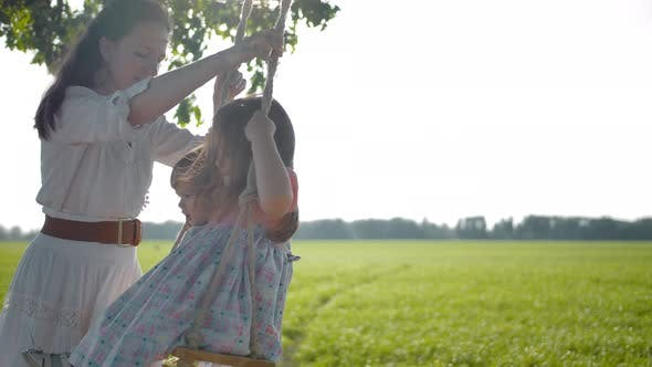 Thumbnail for Kind Happy Mother in White Authentic Dress Shakes Her Pretty Daughters on Swing in the Field