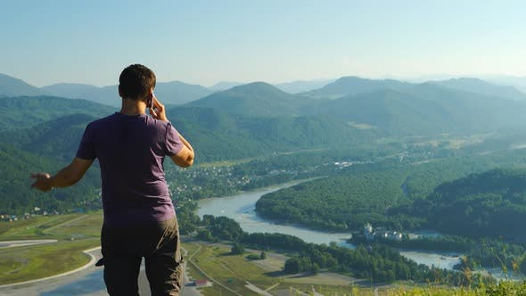 Thumbnail for Young Man Is Talking On A Mobile Phone On A Mountain Landscape Background