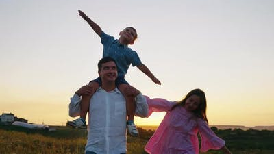 Cheerful Family Together in Countryside at Sunset