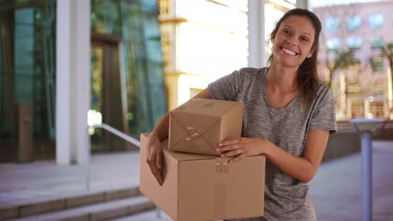 Thumbnail for Beautiful young woman standing outside office building holding shipping boxes