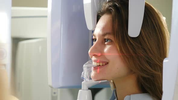 Dental Jaw Scanning. Laser Lines on Patient Face. Female Patient Undergoing Panoramic X-ray