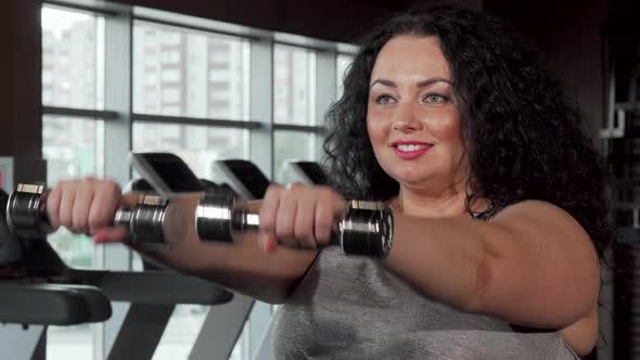 Thumbnail for Happy Plus Size Sportswoman Lifting Dumbbells at the Gym