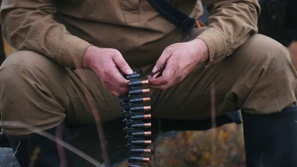 Thumbnail for A Man Soldier Prepares the Ammunition for the Charge in the Machine Gun