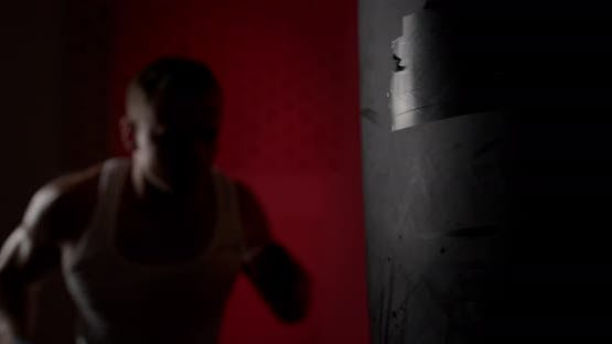 A man in a semi-dark hall, wearing hand wraps, hits a punching bag with quick and accurate punches.