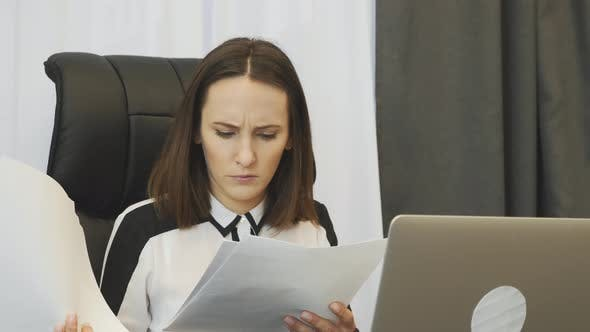 Thumbnail for Shocked female boss looking at financial report. Corporate business concept