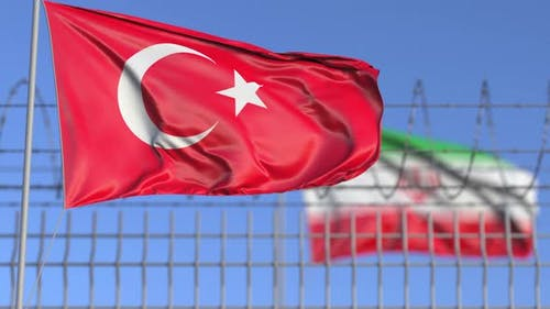 Waving Flags of Turkey and Iran Separated By Barbed Wire Fence