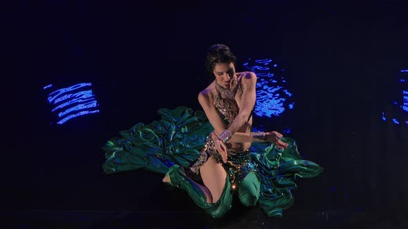 Top View of a Wet Oriental Woman Sitting on the Surface of the Water and Dancing a Belly Dance