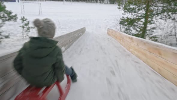 Thumbnail for Camera Following Boy Sledding in Winter
