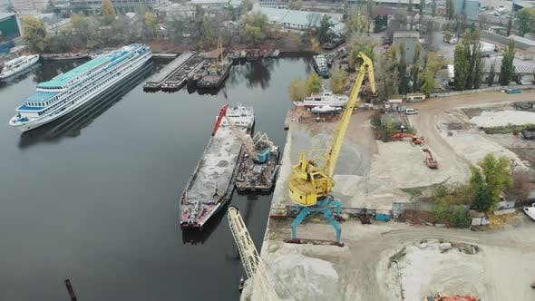 Four working industrial cranes in docks near pile of sand moving sand from barge to trucks