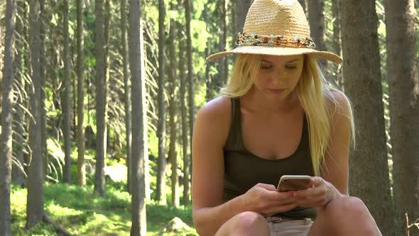 Thumbnail for A Young Beautiful Woman Sits in a Forest on a Sunny Day and Works on a Smartphone