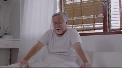 Asian Elderly man wake up and happy in bedroom.