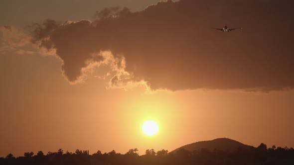 Evening Sky with Golden Sun and Flying Airplane