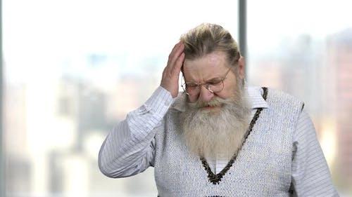 Unhappy Elderly Man Suffering From Headache.