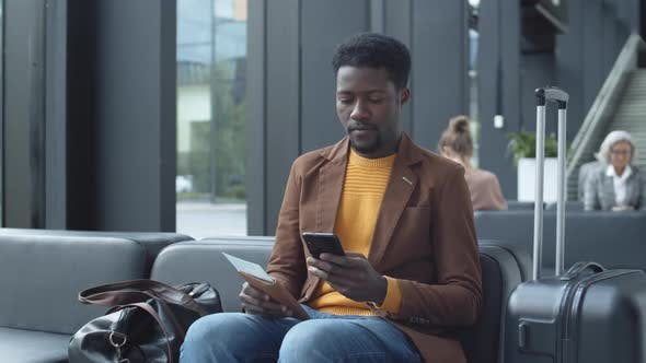African Man Using Cellphone while Waiting in Airport