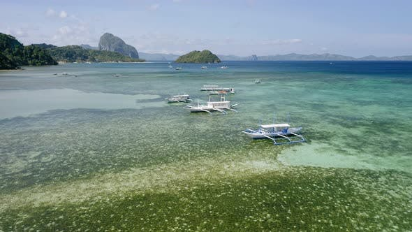 Thumbnail for Aerial Drone View of Boats Anchored in Shallow Water Clear Emerald Green Lagoon. Corong Beach, El