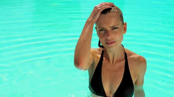 Cover Image for Elegant Female Model in the Swimming Pool Brushing Hair Up in Slow Motion