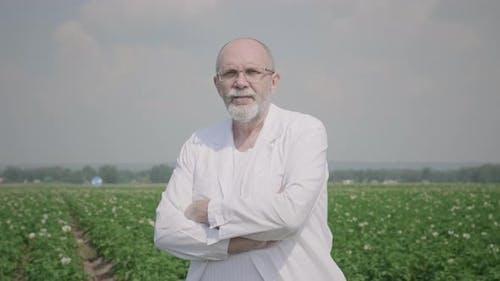 Portrait of senior man in lab coat outdoors