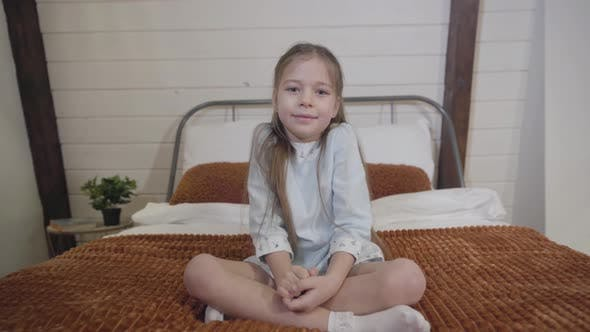 Thumbnail for Camera Approaching To Cute Brunette Caucasian Girl with Grey Eyes Sitting on Bed and Looking at