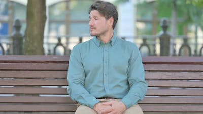 Man Sitting Outdoor and Waiting